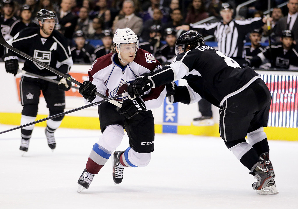 . Colorado Avalanche\'s Nathan MacKinnon, left, is defended by Los Angeles Kings\' Drew Doughty during the first period of an NHL hockey game on Saturday, Nov. 23, 2013, in Los Angeles.(AP Photo/Jae C. Hong)