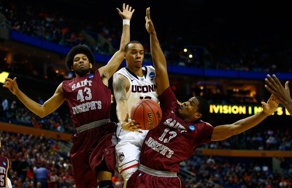 . BUFFALO, NY - MARCH 20: Shabazz Napier #13 of the Connecticut Huskies goes to the basket as DeAndre Bembry #43 and Ronald Roberts, Jr. #13 of the Saint Joseph\'s Hawks defend during the second round of the 2014 NCAA Men\'s Basketball Tournament at the First Niagara Center on March 20, 2014 in Buffalo, New York.  (Photo by Jared Wickerham/Getty Images)