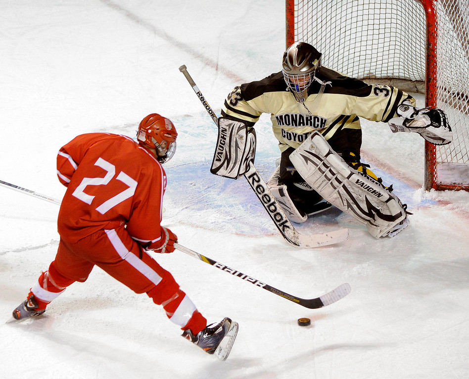 . DENVER, CO. - FEBRUARY 28: Raiders forward Connor Brennan (27) pressured Monarch goalie Ian Oden (33) in the first period. Monarch High School met Regis Jesuit Thursday night, February 28, 2013 in a semifinal match in the Colorado State Ice Hockey Championships at Magness Arena in Denver.  (Photo By Karl Gehring/The Denver Post)