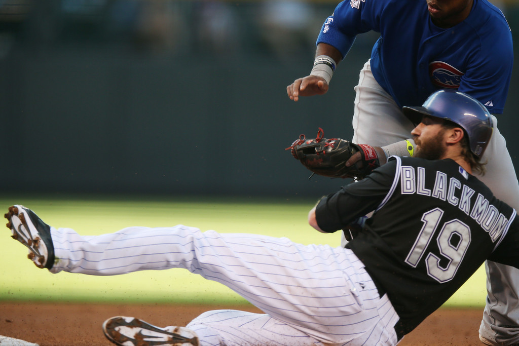 . Colorado Rockies\' Charlie Blackmon, front, is tagged out as he tries to steal third base by Chicago Cubs third baseman Luis Valbuena in the first inning of a baseball game in Denver on Wednesday, Aug. 6, 2014. (AP Photo/David Zalubowski)