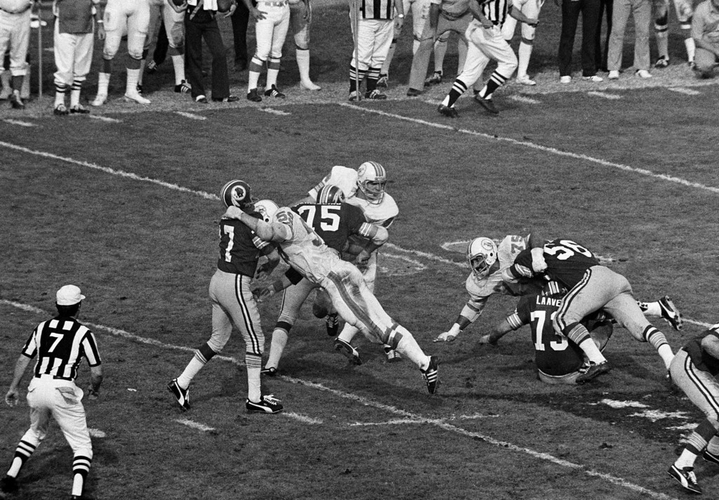 . Washington Redskins\' quarterback Bill Kilmer (17) is hit by Miami Dolphins\' Doug Swift (59), left, just after getting off pass which has intercepted by Dolphins\' Nick Buoniconti (85), right, during Super Bowl game in Los Angeles Sunday, Jan. 15, 1973. Redskins\' John Wilbur goes after Buoniconti. Dolphins w on 24-7. (AP Photo)
