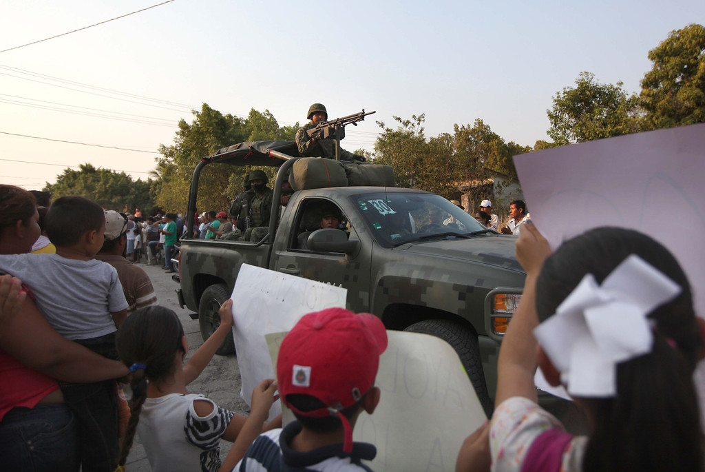 . Mexican army soldiers enter the town of La Ruana, Michoacan, Mexico, Monday, May 20, 2013. Residents of western Mexico towns who endured months besieged by a drug cartel are cheering the arrival of hundreds of Mexican army troops. Hundreds of people in the state of Michoacan have taken up arms to defend their villages against drug gangs, a vigilante movement born of frustration at extortion, killings and kidnappings in a region wracked by violence. (AP Photo/Marco Ugarte)