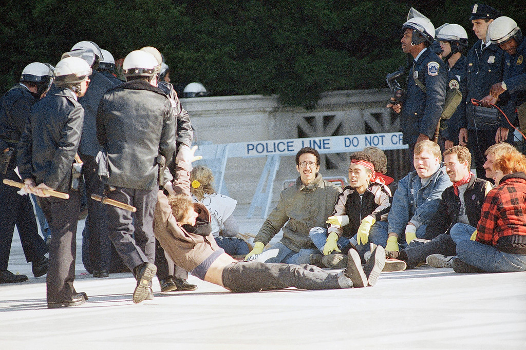 . Police arrest a member of a gay activities group that was demonstrating and attempting to block the entrance to the Supreme Court, Tuesday, Oct. 13, 1987, Washington, D.C. Several hundred took part in the protest. (AP Photo/Scott Stewart)