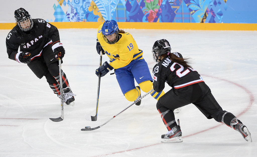 . Sweden\'s Maria Lind (C) controls the puck between Japan\'s Kanae Aokin (R) and Japan\'s Ami Nakamura during the Women\'s Ice Hockey Group B match Sweden vs Japan at the Shayba Arena during the Sochi Winter Olympics on February 9, 2014.  ANDREJ ISAKOVIC/AFP/Getty Images