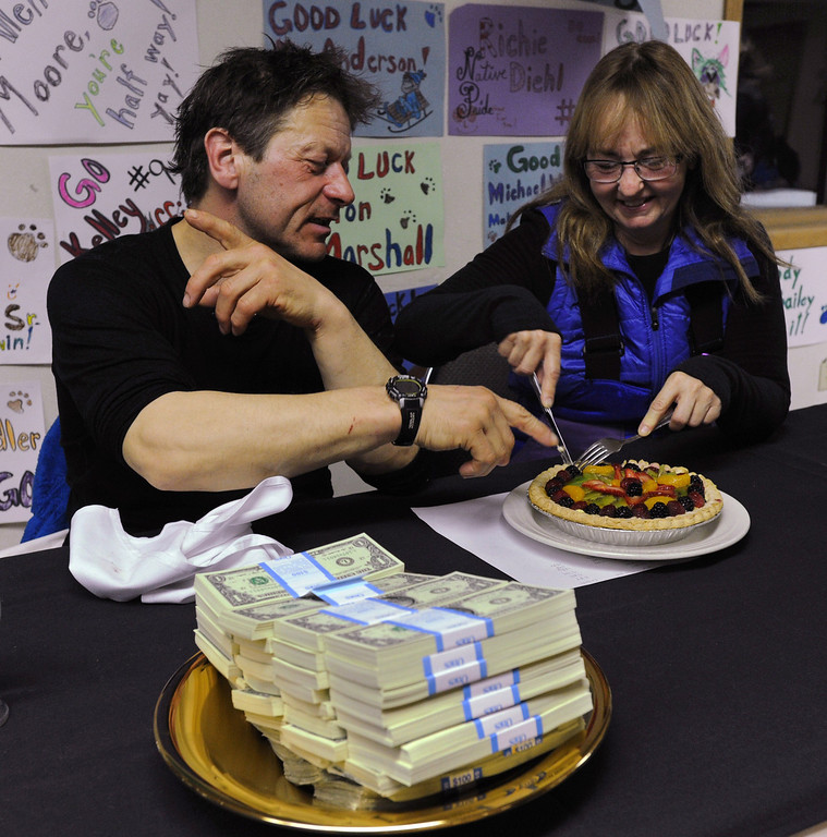 . Four-time Iditarod champion Martin Buser and his wife, Kathy Chapoton, eat a special meal prepared for the First to the Yukon award winner in Anvik, Alaska, during the Iditarod Trail Sled Dog Race, early Friday, March 8, 2013. Besides the meal, there are two more gifts for the first musher: $3,500, served on a gold pan, but all in single $1 bills, and a bottle of champagne. (AP Photo/Anchorage Daily News, Bill Roth)