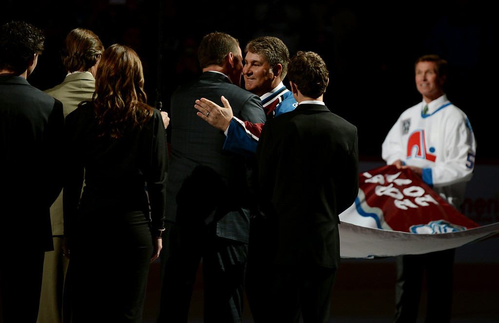 . Ray Bourque, second from front right, hugs his teammate Adam Foote, former Colorado Avalanche defenseman, during the retirement ceremony at Pepsi Center. The Avalanche retired Foote\'s number 52 jersey. (Photo by Hyoung Chang/The Denver Post)
