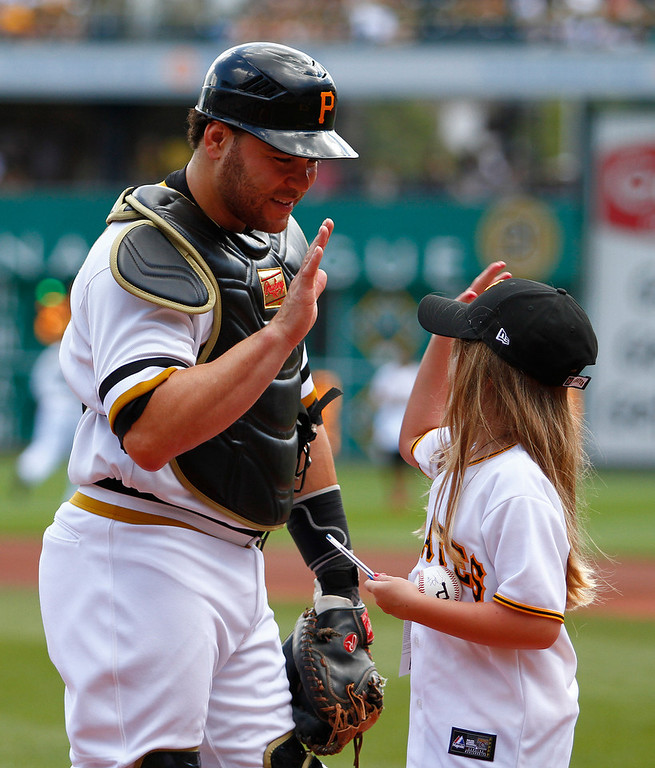 . Russell Martin #55 of the Pittsburgh Pirates high fives a young Pirates fan before the game against the Colorado Rockies on August 4, 2013 at PNC Park in Pittsburgh, Pennsylvania.  (Photo by Justin K. Aller/Getty Images)