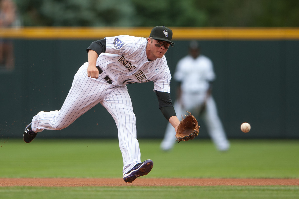 . DENVER, CO - JUNE 16:  Josh Rutledge #14 of the Colorado Rockies fields a ground ball before putting the runner out at first in the first inning of a game against the Philadelphia Phillies at Coors Field on June 16, 2013 in Denver, Colorado.  (Photo by Dustin Bradford/Getty Images)