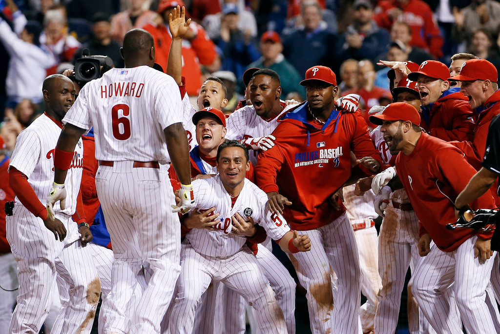 . Philadelphia Phillies players celebrate and wait for Ryan Howard, left, to cross home plate after Howard\'s game-winning three-run home run off Colorado Rockies relief pitcher Boone Logan during the ninth inning of a baseball game, Wednesday, May 28, 2014, in Philadelphia. Philadelphia won 6-3. (AP Photo/Matt Slocum)