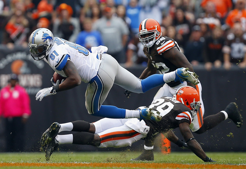 . Wide receiver Calvin Johnson #81 of the Detroit Lions dives for extra yardage as he is hit by defensive back Tashaun Gipson #39 and linebacker D\'Qwell Jackson #52 the Cleveland Browns at FirstEnergy Stadium on October 13, 2013 in Cleveland, Ohio.  (Photo by Matt Sullivan/Getty Images)