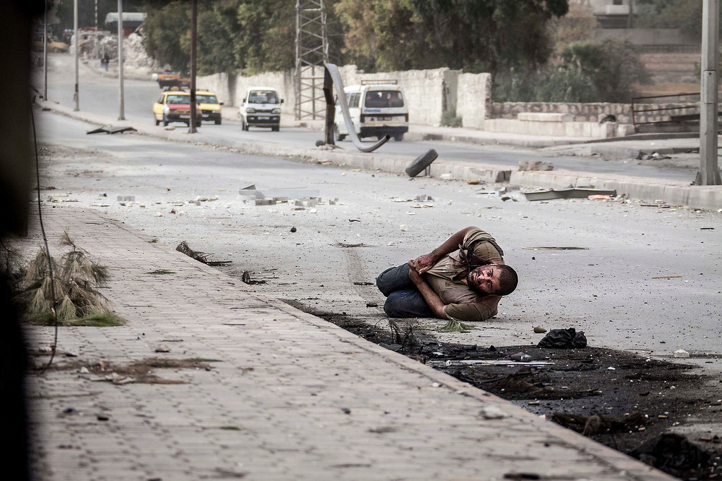 . FILE - A wounded Syrian civilian lies in the street with a shot to his stomach as he tries to escape the line-of-fire after he was targeted by a Syrian army sniper while walking near the frontline in the Bustan al-Qasr neighborhood of Aleppo, Syria, Saturday, Oct. 20, 2012. (AP Photo/Narciso Contreras, File)