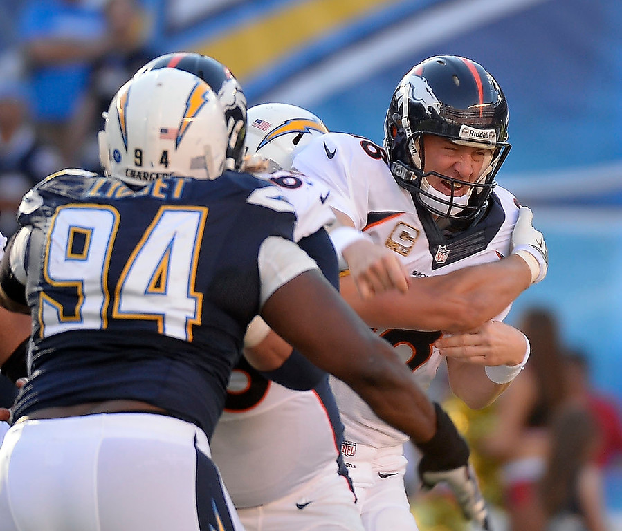 . Denver Broncos quarterback Peyton Manning (18) gets hit hard after a throw during the third quarter against the San Diego Chargers at Qualcomm Stadium. (Photo by John Leyba/The Denver Post)