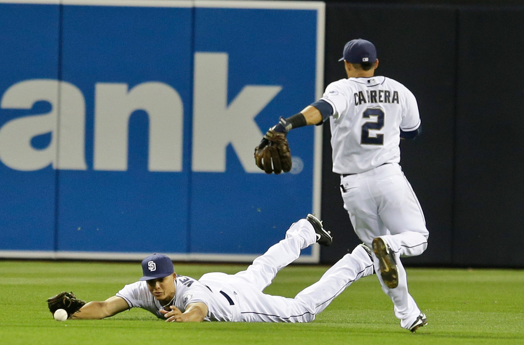 . San Diego Padres center fielder Will Venable can not make the diving catch on a bloop single by Colorado Rockies\' Michael Cuddyer that drove in a run during the first inning of a baseball game, Friday, April 12, 2013, in San Diego. (AP Photo/Lenny Ignelzi)