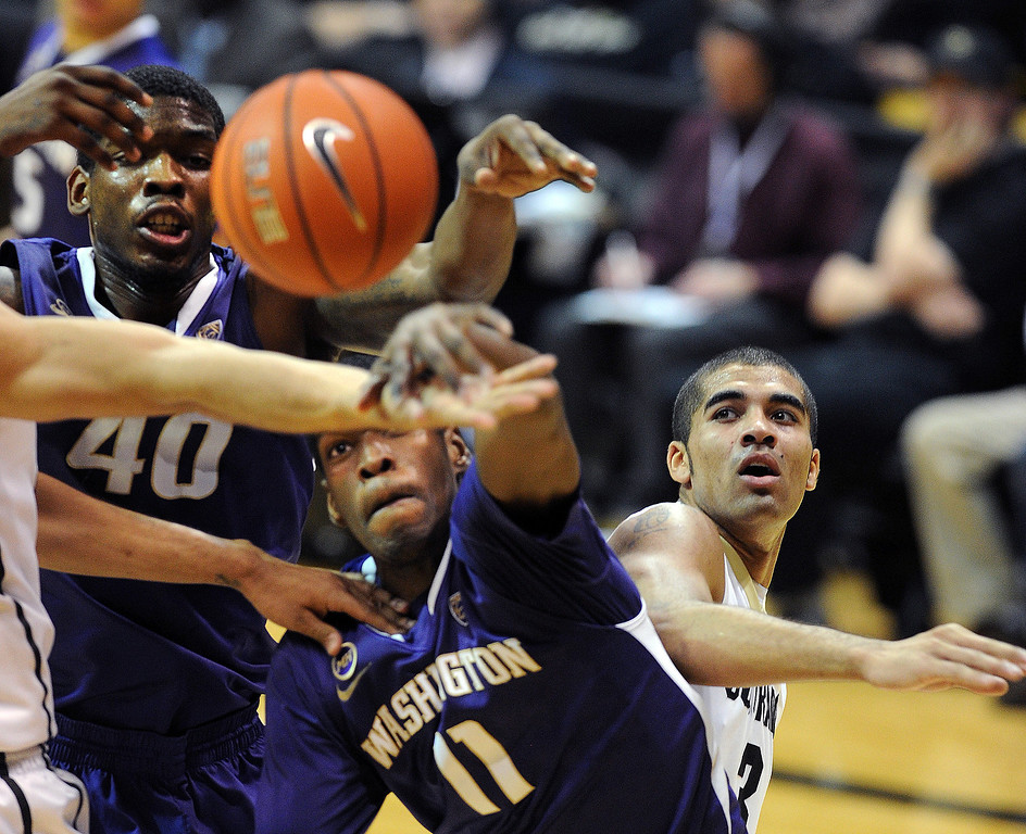 . Shawn Kemp, left, Mike Anderson, both of Washington, and Xavier Talton of Colorado, battle under the boards during the second half of an NCAA college basketball game in Boulder, Colo., Sunday, Feb. 9, 2014. (AP Photo/Daily Camera, Cliff Grassmick)