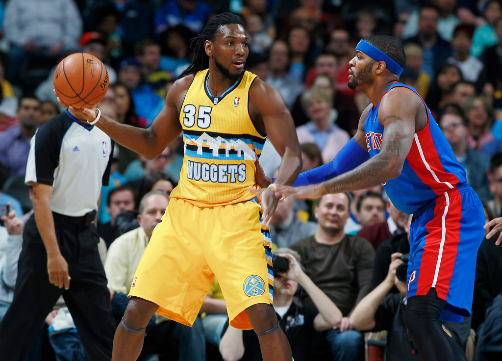 . Denver Nuggets forward Kenneth Faried, left, looks to pass ball as Detroit Pistons forward Josh Smith covers in the first quarter of an NBA basketball game in Denver on Wednesday, March 19, 2014. (AP Photo/David Zalubowski)