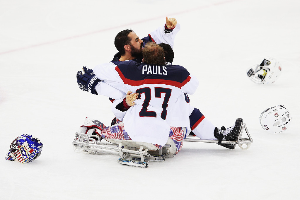 . Steve Cash of the USA and Nikko Landeros of the USA and Joshua Pauls of the USA celebrate after winning the ice sledge hockey gold medal game between the Russian Federation and the United States of America at the Shayba Arena during day eight of the 2014 Paralympic Winter Games on March 15, 2014 in Sochi, Russia.  (Photo by Hannah Peters/Getty Images)
