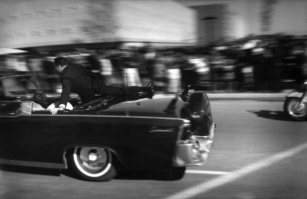 . Secret Service agent Clinton Hill stands over the president as the limousine rushes toward the hospital seconds after Kennedy was shot. In the jump seat, Nellie Connally bends over wounded Texas Gov. John Connally, and the first lady tries to assist the mortally wounded president.  Justin Newman, Associated Press file