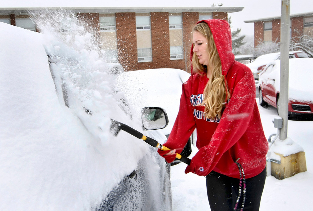 . Shenandoah University freshman, Erin Septer brushes the snow off her car outside her dorm on Tuesday, Jan. 21, 2014, as snow falls in Winchester, Va. (AP Photo/The Winchester Star, Ginger Perry)