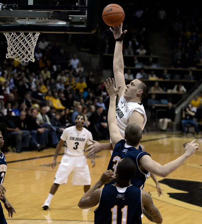 . University of Colorado\'s Shane Harris-Tunks takes a shot over Max Jacobsen during a game against Northern Arizona on Friday, Dec. 21, at the Coors Event Center on the CU campus in Boulder.  (Jeremy Papasso/Daily Camera)