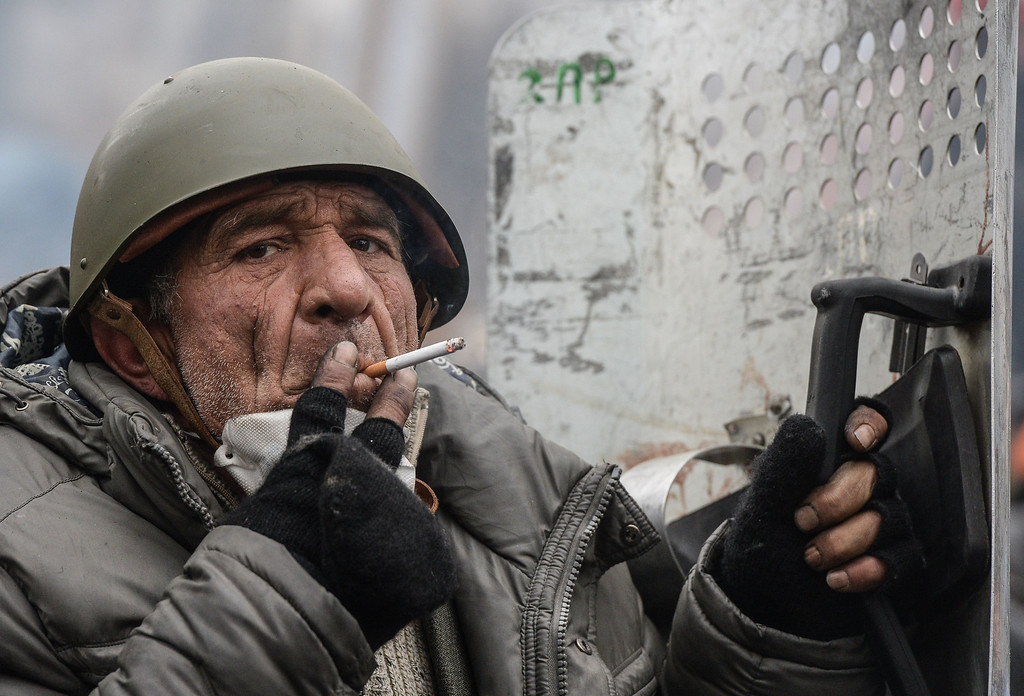 . An elderly protester smokes during a break in clashes with police in central Kiev on February 20, 2014. Armed protesters stormed today police barricades in Kiev, leaving at least one person dead and shattering a fragile truce as EU foreign ministers called off a crisis meeting with the embattled Ukrainian president. AFP PHOTO / DMITRY  SEREBRYAKOV/AFP/Getty Images