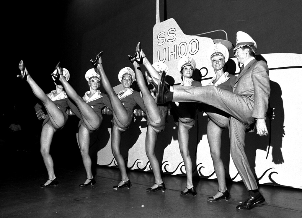 . Georgia Gov. Jimmy Carter joins a half-dozen rockettes in a high kick, September 21, 1973, at Radio City Music Hall in New York, while visiting backstage before an afternoon performance.  Carter is in New York to induce the film industry to make pictures in his state.  (AP Photo/stf)