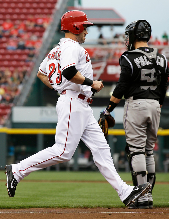 . Cincinnati Reds\' Skip Schumaker (25) scores past Colorado Rockies catcher Jordan Pacheco on a sacrifice fly hit by Brandon Phillips in the first inning of a baseball game on Friday, May 9, 2014, in Cincinnati. (AP Photo/Al Behrman)