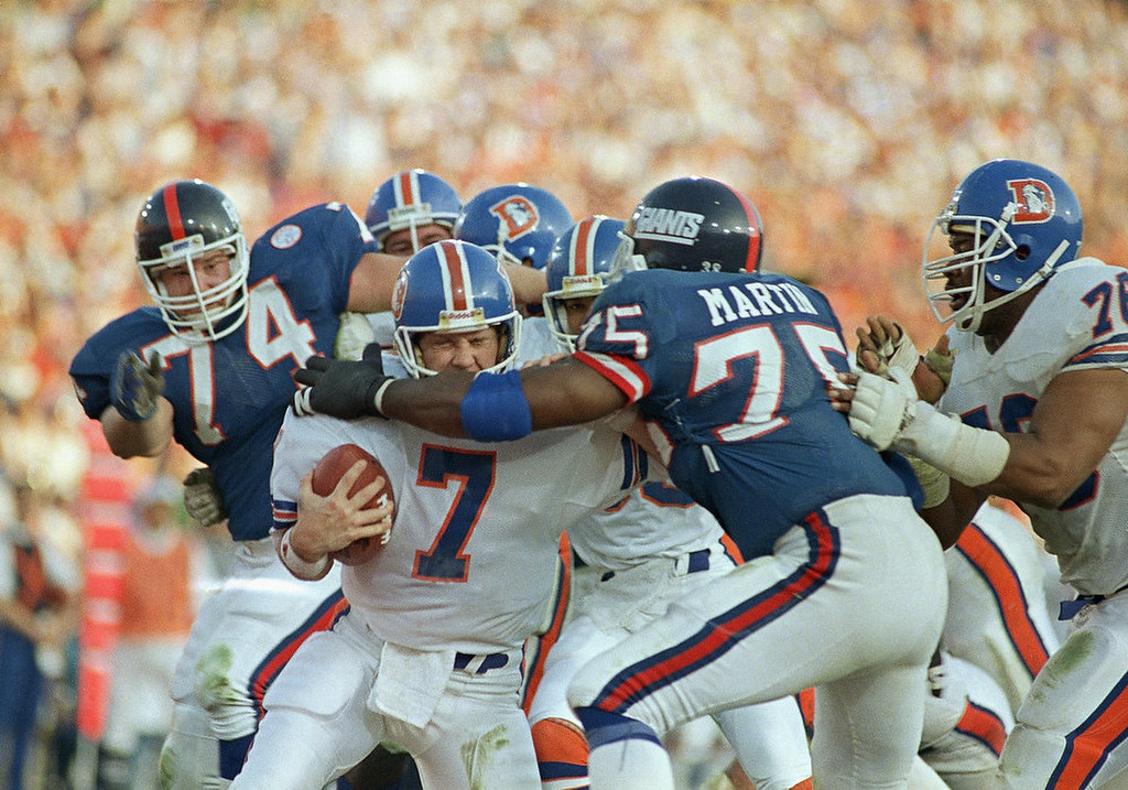 . Denver Broncos quarterback John Elway gets sacked for a safety by New York Giants left end George Martin (75) in the second quarter of Super Bowl XXI, Jan. 25, 1987 in Pasadena, Calif. (AP Photo/Lennox Mclendon)