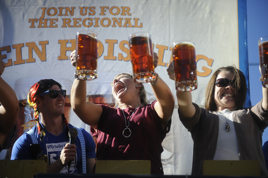 ". DENVER, CO: Sept 28, 2013  Johnna Mathena and Jessica Woolery struggle to hold their steins up during the Stein Hoisting competition at Denver\'s Oktoberfest. ""It\'s not as easy as it looks,\"" Mathena said.   (Photo By Erin Hull/The Denver Post)"