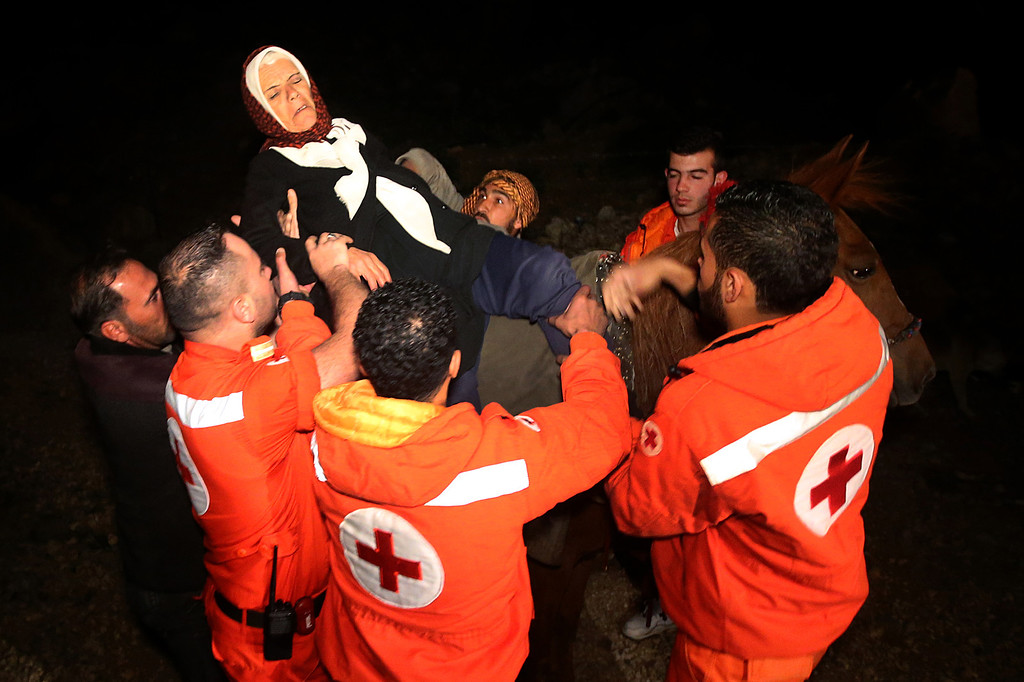 . In this picture taken early Sunday, April 20, 2014, Farizeh Kabalan, 74, who fled her home in the Syrian village of Beit Jinn near the Israeli-occupied Golan Heights, is lifted from a horse by Lebanese Red Cross volunteers after descending from the 2,814-meter (9,232-foot) high Mount Hermon (Jabal el-Sheikh), into the town of Chebaa in southeast Lebanon. The village of Beit Jinn, where most of the fleeing Syrians came from, has been under siege by Syrian troops for months, and no food and medicine has been allowed to reach thousands of trapped civilians inside. (AP Photo/Hussein Malla)