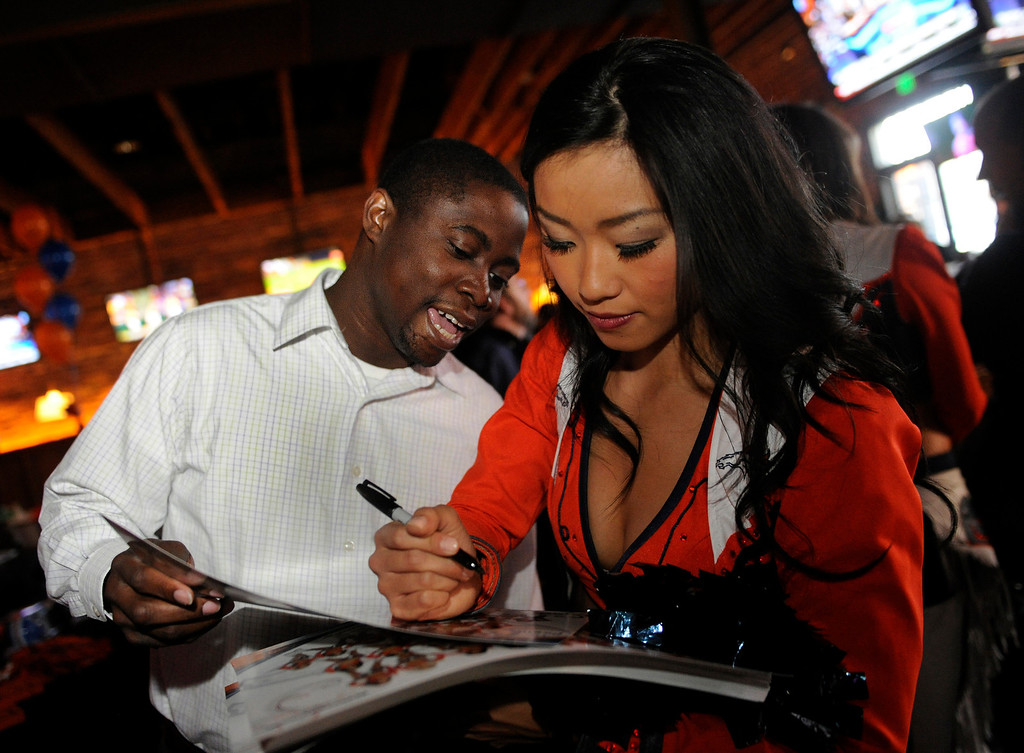 . Ramon Browne got an autograph from Kisa, a Denver Broncos cheerleader, Thursday night. Broncos fans gathered for a NFL draft party at the Tavern Downtown, 1949 Market Street, Thursday night, April 25, 2013. Photo By Karl Gehring/The Denver Post