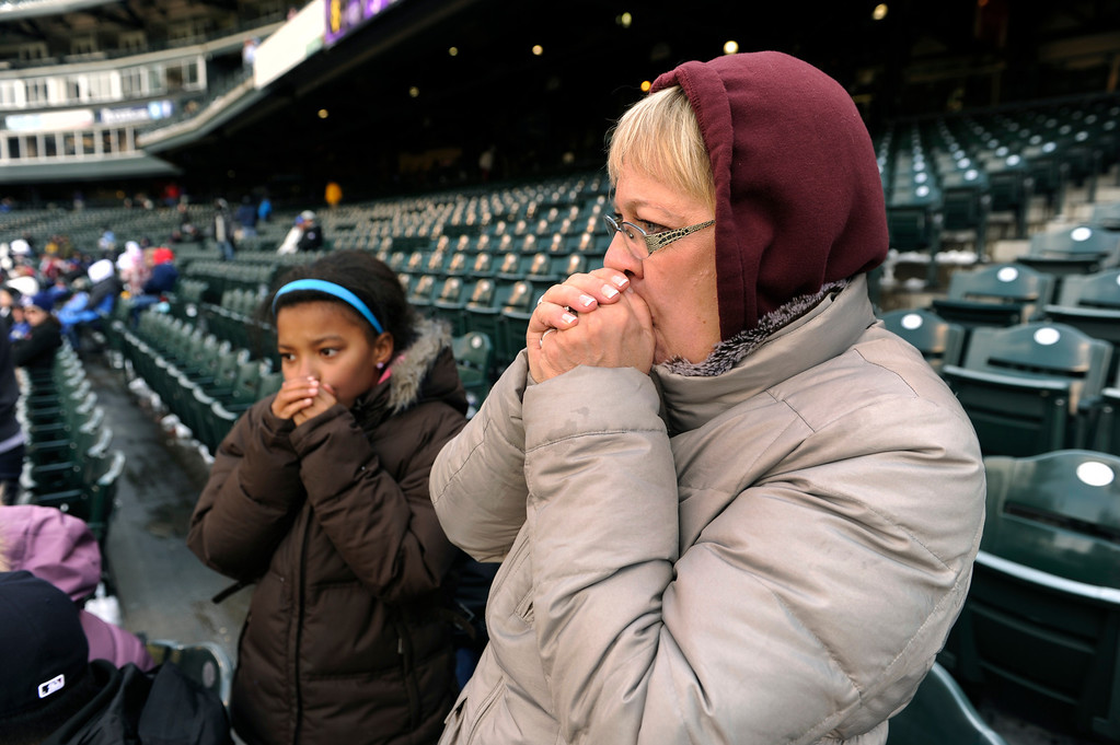 . DENVER, CO. - APRIL 23:  Lola Nordhagen, left, and her grandmother Starla Solberg, right, both blew on their hands to keep warm during the seventh inning. The temperature at the ballpark never climbed above freezing during the game. The Atlanta Braves defeated the Colorado Rockies 4-3 at Coors Field Tuesday, April 23, 2013.  The first game of the doubleheader Tuesday was a make-up from Monday night\'s postponement due to weather.  Photo By Karl Gehring/The Denver Post
