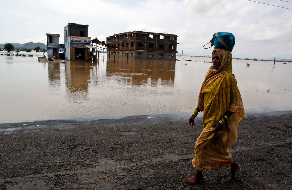 . An Indian villager walks towards her village past floodwaters in Ganjam district of Orissa state, India, Saturday, Oct. 26, 2013. As of Saturday, 39 people had died in flood-related incidents in Andhra Pradesh and Orissa states since the rains began Monday, according to officials quoted by the Press Trust of India. (AP Photo/Biswaranjan Rout)