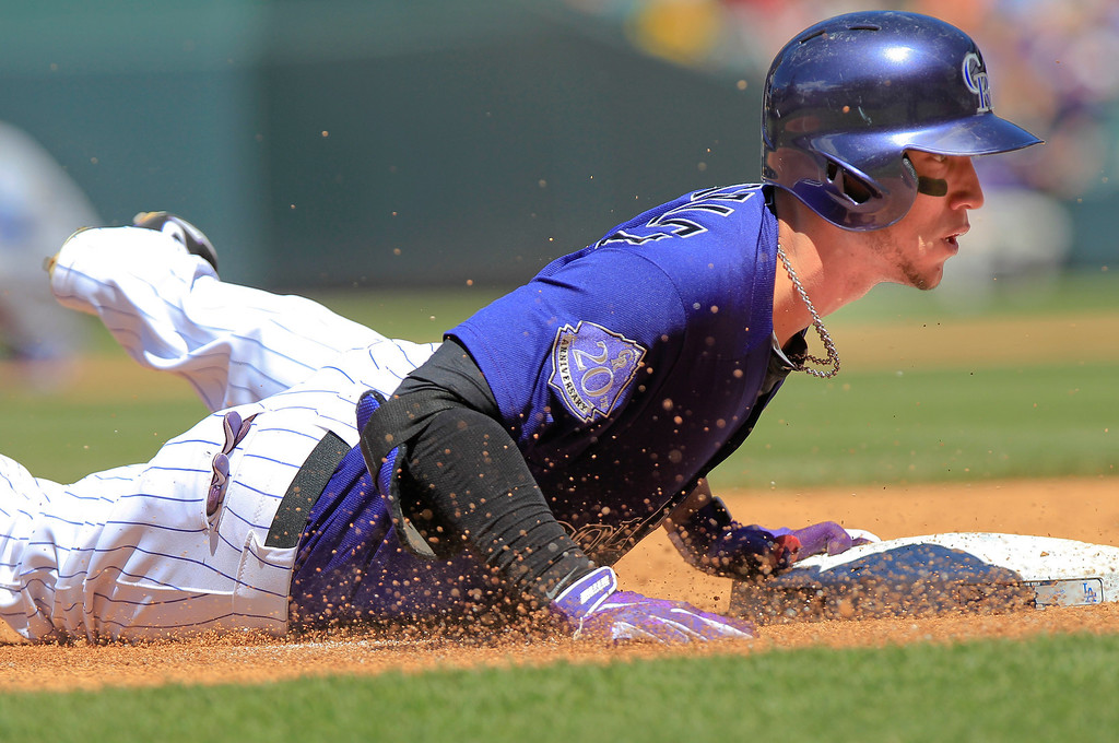 . Colorado Rockies\' Carlos Gonzalez (5) slides into third after hitting a triple off of Los Angeles Dodgers starting pitcher Zack Greinke (21) during the third inning of the MLB National League baseball game Saturday June 1, 2013, in Denver. (AP Photo/Barry Gutierrez)