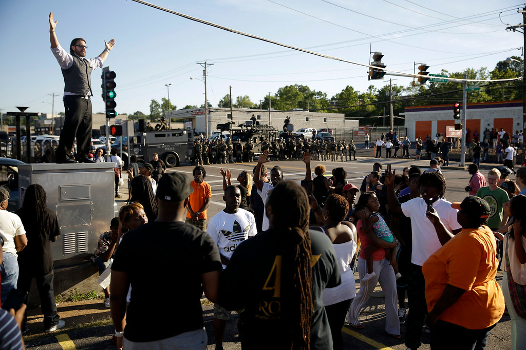 . A man tries to calm a group of protesters as police stand in the distance in Ferguson, Mo. on Wednesday, Aug. 13, 2014. On Saturday, Aug. 9, 2014, a white police officer fatally shot Michael Brown, an unarmed black teenager. (AP Photo/Jeff Roberson)
