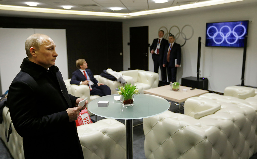 . Russian President Vladimir Putin waits in the presidential lounge to be introduced at the opening ceremony of the 2014 Winter Olympics, Friday, Feb. 7, 2014, in Sochi, Russia. (AP Photo/David Goldman, Pool)