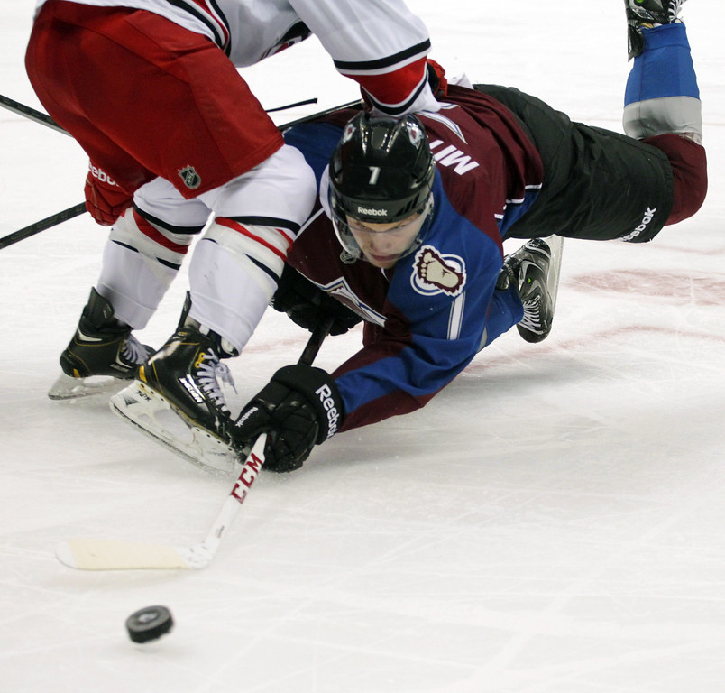 . Colorado Avalanche center John Mitchell (7) dives for the puck against Carolina Hurricanes center Nathan Gerbe (14) in the second period of an NHL hockey game in Denver on Friday, Oct. 25, 2013.(AP Photo/Joe Mahoney)