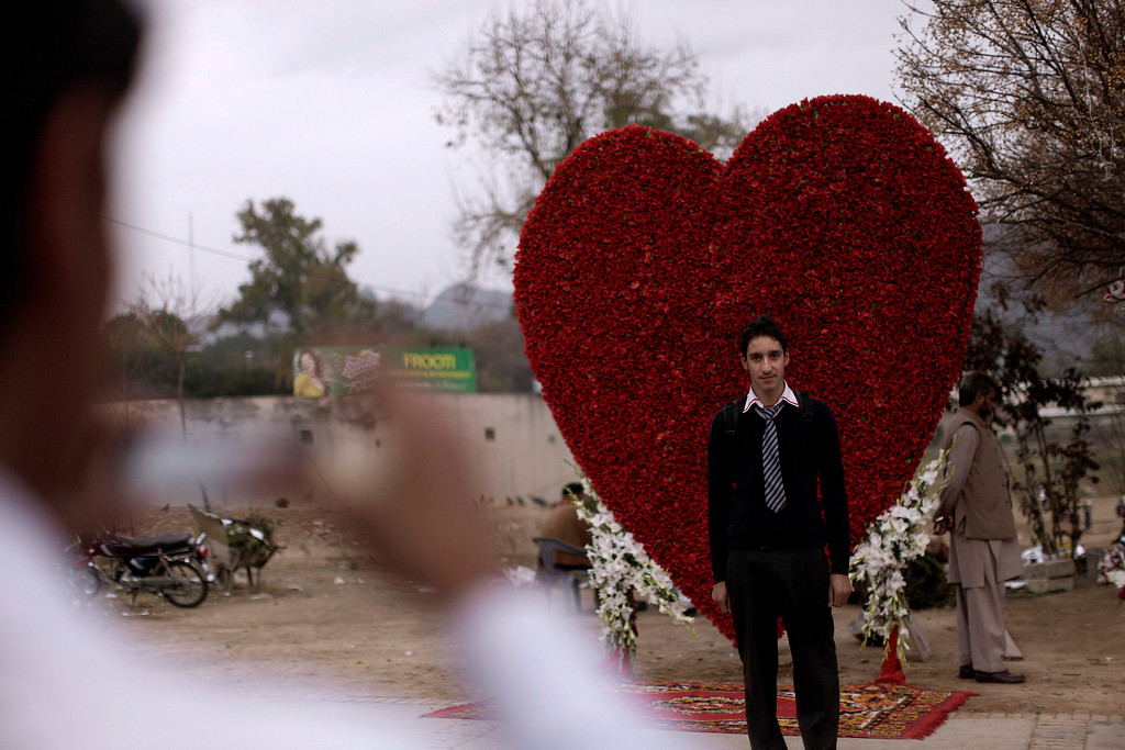 . A Pakistani youth poses for a picture taken by his friend in front of a big red heart made of flowers displayed outside flowers shop on Valentine\'s Day, in Islamabad, Pakistan, Thursday, Feb. 14, 2013.  (AP Photo/Muhammed Muheisen)
