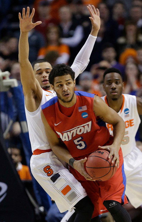 . Dayton\'s Devin Oliver (5) passes away from Syracuse\'s Tyler Ennis during the first half of a third-round game in the NCAA men\'s college basketball tournament in Buffalo, N.Y., Saturday, March 22, 2014. (AP Photo/Frank Franklin II)