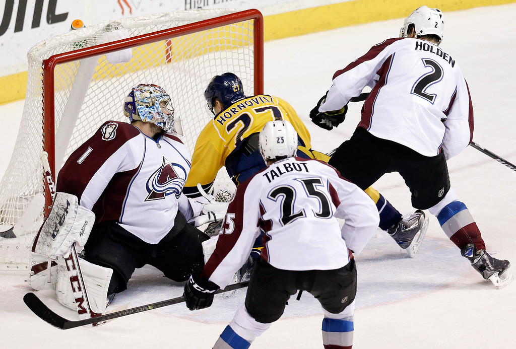 . Nashville Predators forward Patric Hornqvist (27), of Sweden, falls into Colorado Avalanche goalie Semyon Varlamov (1), of Russia, as Hornqvist scores a goal in the second period of an NHL hockey game, Saturday, Jan. 18, 2014, in Nashville, Tenn. Also defending for the Avalanche are Maxime Talbot (25) and Nick Holden (2). (AP Photo/Mark Humphrey)
