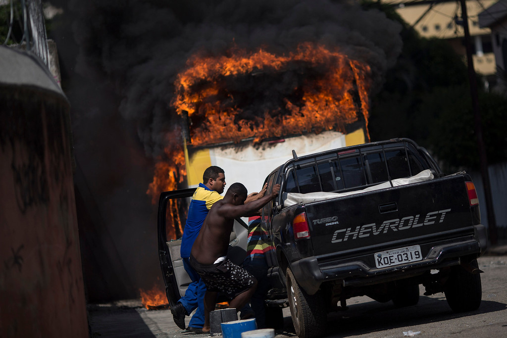 . Men move a car away from a burning bus that was set on fire near the area recently occupied by squatters in Rio de Janeiro, Brazil, Friday, April 11, 2014. Squatters in Rio de Janeiro are clashing with police after a Brazilian court ordered that 5,000 people be evicted from abandoned buildings of a telecommunications company. Officers have used tear gas and stun grenades to try to disperse the families. (AP Photo/Felipe Dana)