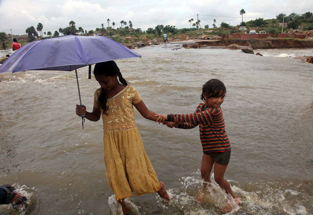 . Indian girls wade through a flood-damaged road on the outskirts of Hyderabad, in the southern Indian state of Andhra Pradesh, Saturday, Oct. 26, 2013. Days of torrential rains have unleashed floods in the states of Andhra Pradesh and Orissa, killing dozens of people and forced the evacuation of more than 70,000 others from hundreds of low-lying villages. (AP Photo/Mahesh Kumar A.)