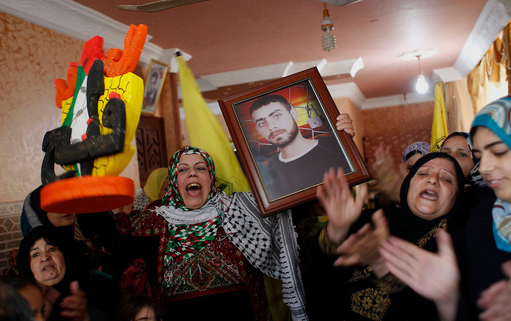 . The mother (C) of Palestinian prisoner Ramy Barbakh, 37, holds his picture in their home in Khan Yunis, in the southern Gaza Strip, on December 29, 2013, after receiving the news of his impending release. Israel approved the release of 26 Palestinian prisoners, the third batch to be freed under the terms of renewed US-brokered peace talks. SAID KHATIB/AFP/Getty Images