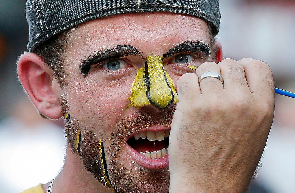 . Barry Hale, right, paints the face of his brother Jake Pickard, both of Wellfleet, Mass., before Game 6 of the NHL hockey Stanley Cup Finals between the Boston Bruins and the Chicago Blackhawks Monday, June 24, 2013, in Boston. (AP Photo/Michael Dwyer)