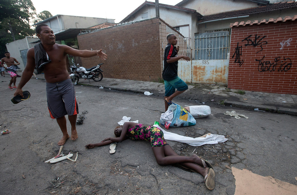 . A woman affected by tear gas lies on the ground during an eviction in Rio de Janeiro, Brazil, Friday, April 11, 2014. Squatters in Rio de Janeiro are clashing with police after a Brazilian court ordered that 5,000 people be evicted from abandoned buildings of a telecommunications company. Officers have used tear gas and stun grenades to try to disperse the families. (AP Photo/Silvia Izquierdo)
