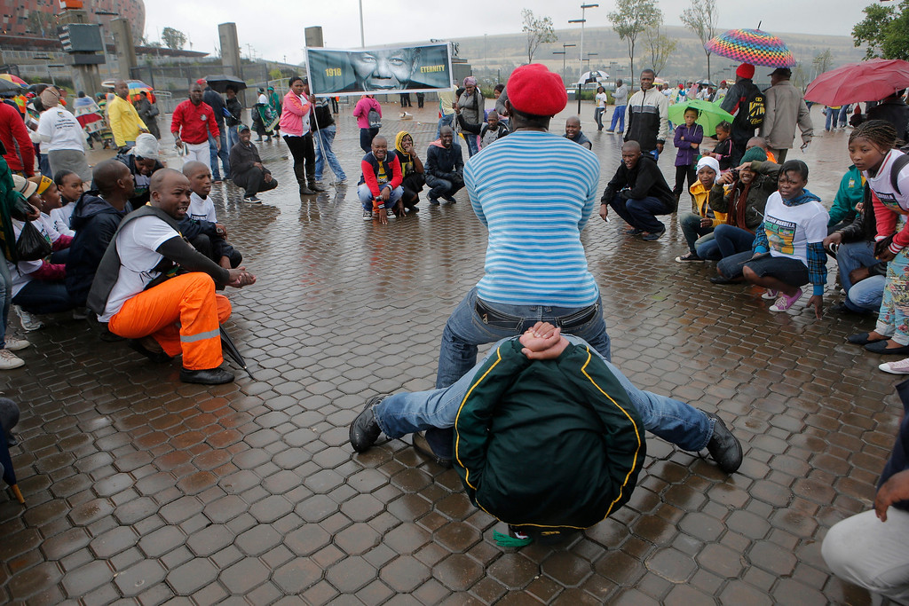 . A youth group performs as people arrive for the memorial service for former South African president Nelson Mandela at the FNB Stadium in Soweto, near Johannesburg, South Africa, Tuesday Dec. 10, 2013. (AP Photo/Tsvangirayi Mukwazhi)