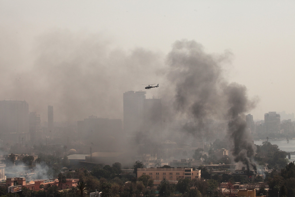 . Smoke rises from the Police Officers Club, left, and the Egyptian Soccer Federation, right, as a police helicopter surveys the scene after protesters set fire following a court verdict in Saturday, March 9, 2013. (AP Photo/Maya Alleruzzo)