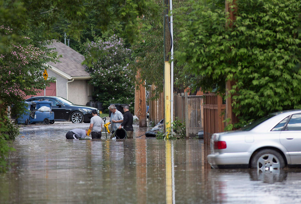 . Residents of Elbow Park try to clear a drain on a flooded street in Calgary, Alberta June 22, 2013.   REUTERS/Todd Korol