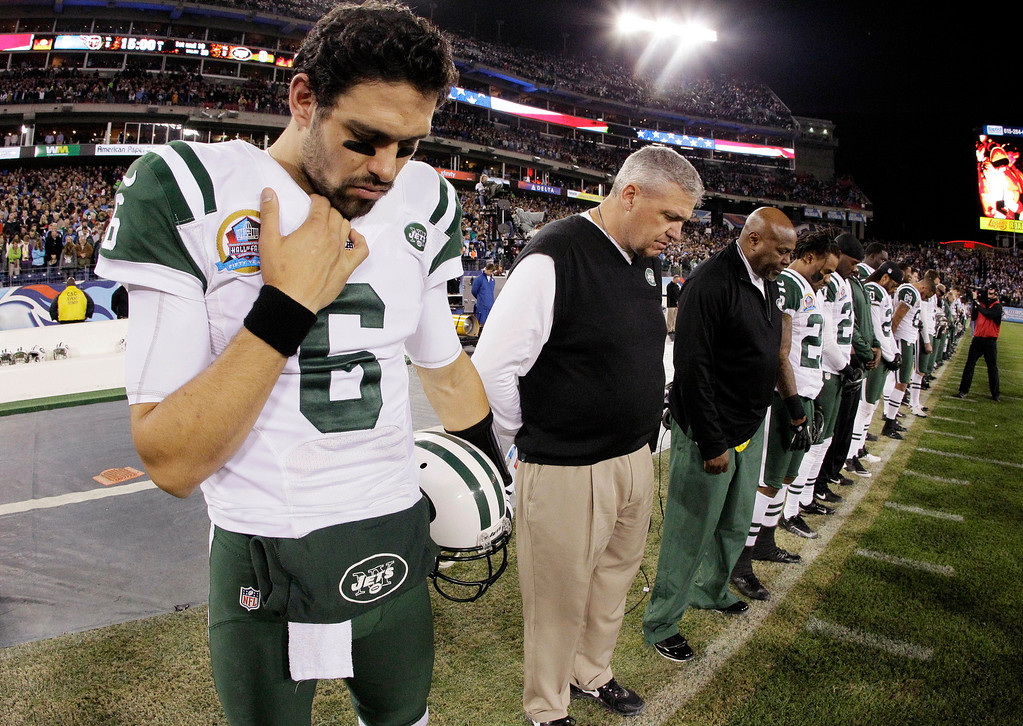 . New York Jets quarterback Mark Sanchez (6) and head coach Rex Ryan bow their heads during a moment of silence for the victims of the Sandy Hook Elementary School shootings in Newtown, Conn., before an NFL football game against the Tennessee Titans, Monday, Dec. 17, 2012, in Nashville, Tenn. (AP Photo/Wade Payne)