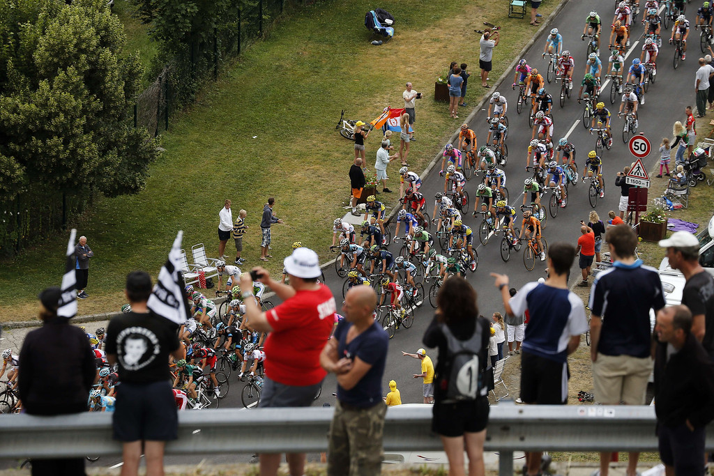 . Supporters cheer cyclists from a bridge as the pack riding during the 204.5 km nineteenth stage of the 100th edition of the Tour de France cycling race on July 19, 2013 between Bourg-d\'Oisans and Le Grand-Bornand, French Alps.  AFP PHOTO / JEFF  PACHOUD/AFP/Getty Images