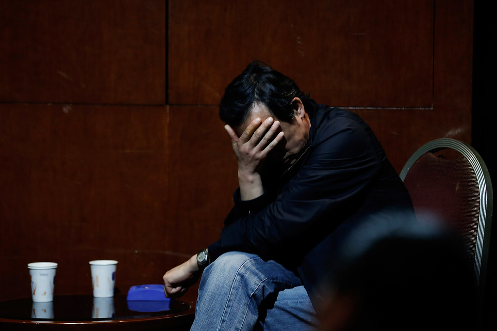 . A family member of a passenger from the missing Malaysia Airlines flight MH370 waits for news at the Lido Hotel on March 20, 2014 in Beijing, China. Australian Prime Minister, Tony Abbott said that authorities have spotted two objects in the Indian Ocean that may be related to flight MH370. The missing aircraft disappeared one week ago carrying 227 passengers and 12 crew on route from Kuala Lumpur to Beijing. All passengers and crew are currently under investigation and 26 countries are involved in the search.  (Photo by Lintao Zhang/Getty Images)